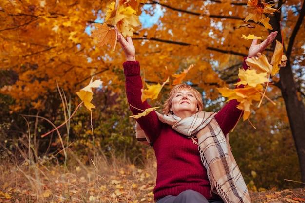 Femme d'âge moyen jetant des feuilles dans la forêt. dame senior heureuse