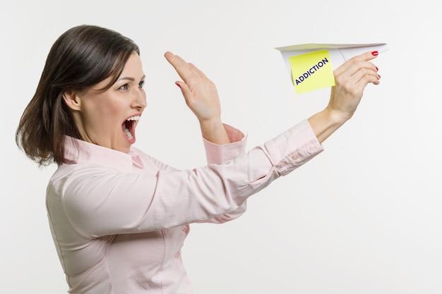Une femme d'âge moyen laisse échapper un avion en papier avec le mot addiction.