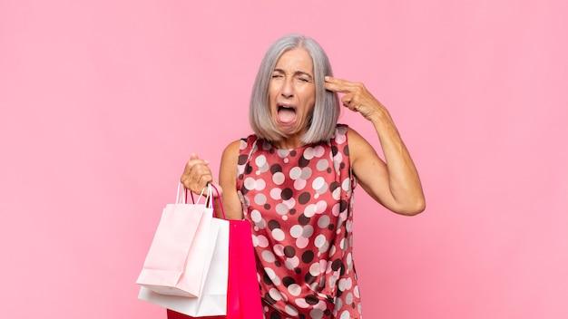 Femme d'âge moyen à la malheureuse et stressée, geste de suicide faisant signe des armes à feu avec la main, pointant vers la tête avec des sacs à provisions