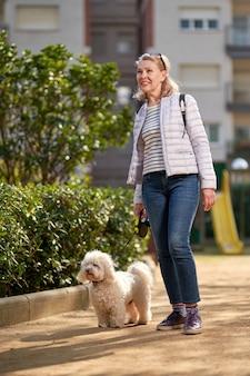 Femme d'âge moyen marchant avec un chien blanc moelleux dans la ville d'été.