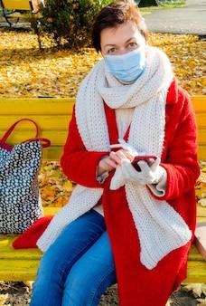 Femme d'âge moyen avec masque médical de protection en automne park
