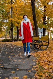 Femme d'âge moyen avec masque médical de protection sur son visage se promène dans le parc de l'automne