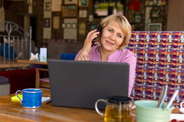 Une femme d'âge moyen avec un ordinateur portable travaille dans un café au bureau, elle est pigiste. femme à lunettes assise à la table avec une tasse de tisane. elle est de bonne humeur.