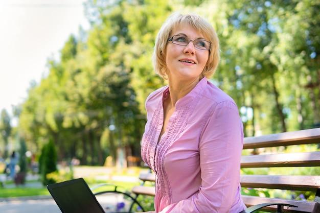 Une femme d'âge moyen avec un ordinateur portable travaille dans le parc