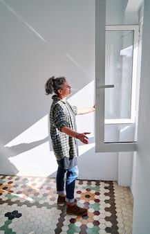 Femme d'âge moyen ouvrant la fenêtre dans une pièce avec un sol hydraulique coloré