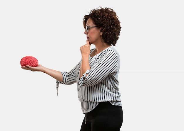 Femme d'âge moyen pensant et déduisant, regardant un cerveau essayant de le comprendre