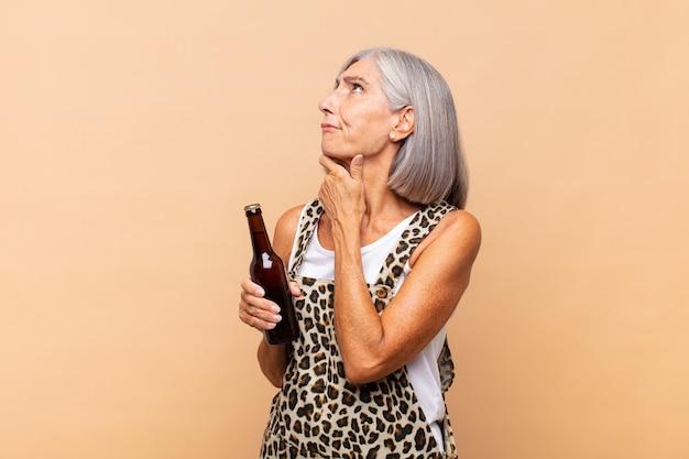 Femme d'âge moyen pensant, doutant et confuse, avec différentes options, se demandant quelle décision prendre avec une bière