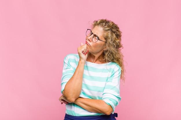 Femme d'âge moyen pensant, doutant et confuse, avec différentes options, se demandant quelle décision prendre