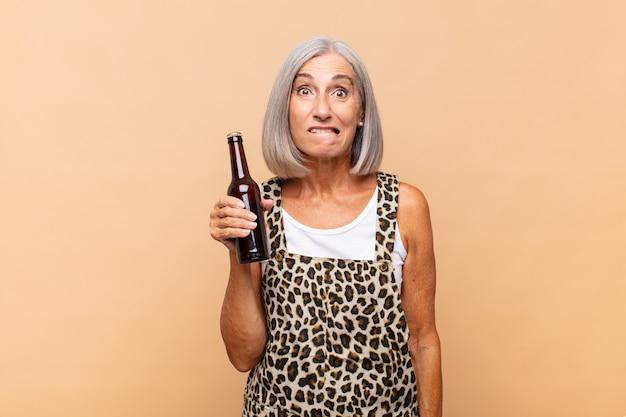 Femme d'âge moyen à la perplexité et à la confusion, mordre la lèvre avec un geste nerveux isolé