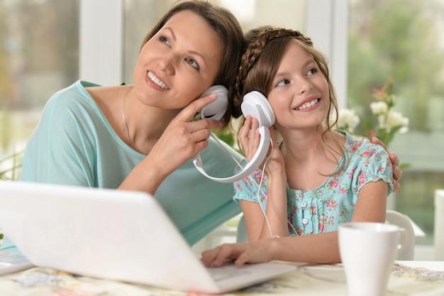Femme d'âge moyen et petite fille écoutant de la musique à l'aide d'un ordinateur portable