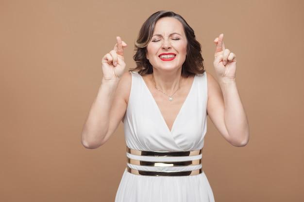 Femme d'âge moyen pleine d'espoir. les mains croisées et les yeux fermés. femme exprimant ses émotions en robe blanche, lèvres rouges et coiffure frisée foncée. prise de vue en studio, à l'intérieur, isolée sur fond beige ou marron clair