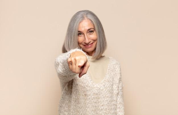 Femme d'âge moyen pointant vers la caméra avec un sourire satisfait, confiant et amical, vous choisissant