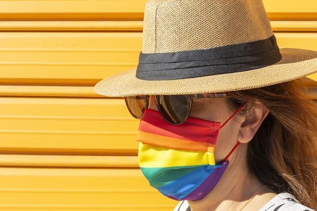 Femme d'âge moyen portant un chapeau, des lunettes de soleil et un masque de protection de couleur arc-en-ciel. lgtb sur fond jaune. concept covid-19