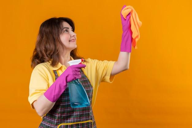 Femme d'âge moyen portant un tablier et des gants en caoutchouc holding spray de nettoyage et nettoyage de tapis avec sourire sur le visage debout sur un mur orange