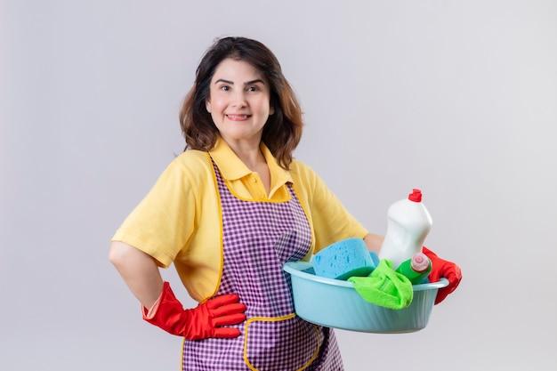 Femme d'âge moyen portant un tablier et des gants en caoutchouc tenant le bassin avec des outils de nettoyage