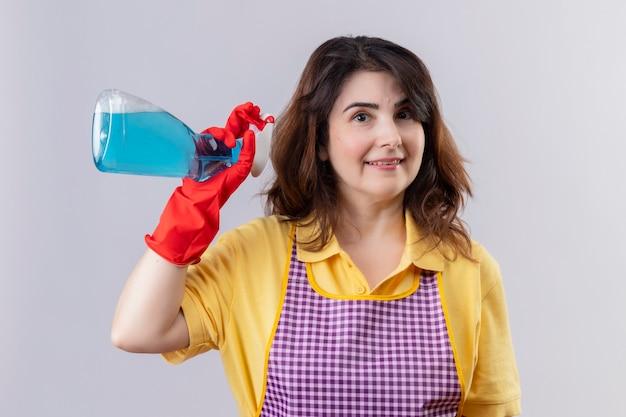 Femme d'âge moyen portant un tablier et des gants en caoutchouc tenant un spray de nettoyage souriant avec un visage heureux debout sur un mur blanc