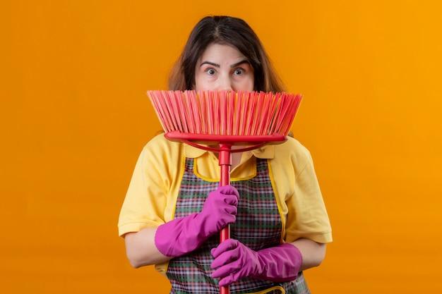 Femme d'âge moyen portant un tablier et des gants en caoutchouc tenant une vadrouille se cachant derrière elle à la surprise debout sur un mur orange