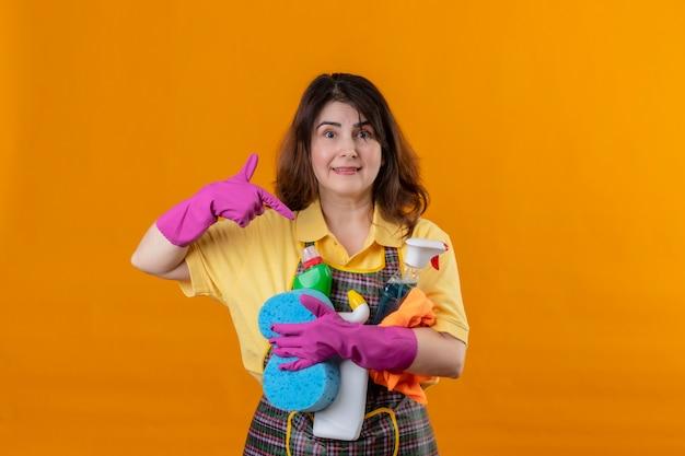 Femme d'âge moyen portant un tablier et des gants ruuber avec des produits de nettoyage pointant avec le doigt pour eux souriant sympathique positif et heureux debout sur le mur orange