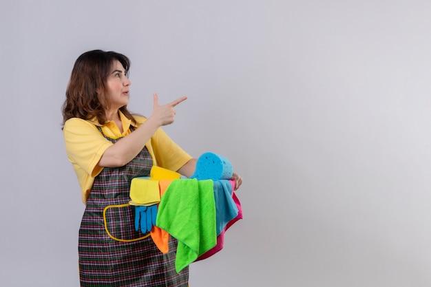 Femme d'âge moyen portant un tablier tenant un seau avec des outils de nettoyage debout sur le côté, pointant vers quelque chose avec le doigt à la surprise sur le mur blanc