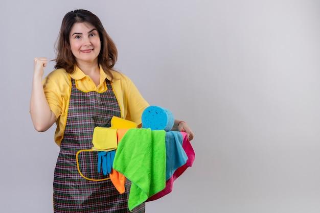 Femme d'âge moyen portant un tablier tenant un seau avec des outils de nettoyage pointant vers quelque chose derrière souriant posotove et heureux debout sur un mur blanc