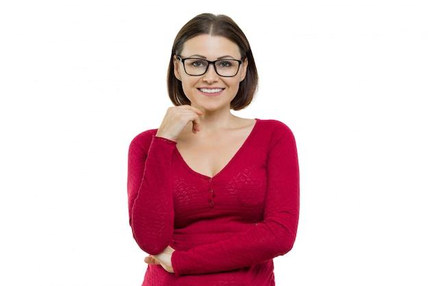 Femme d'âge moyen positive posant avec les mains sur le blanc