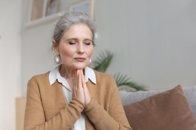 Femme d'âge moyen priant, les yeux ouverts, levant les yeux, espérant le meilleur, demandant pardon.
