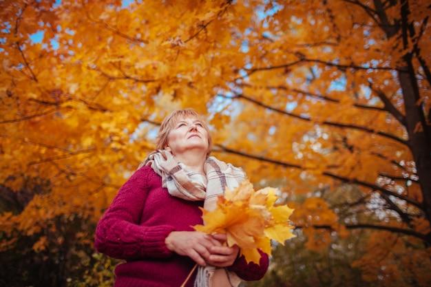 Femme d'âge moyen rassemble des feuilles d'érable. dame marchant et profitant de la nature