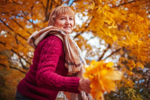 Femme d'âge moyen rassemble des feuilles d'érable. dame marchant et s'amusant