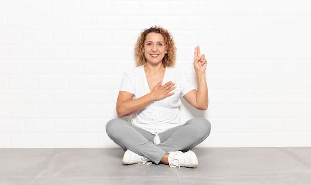 Femme d'âge moyen à la recherche de bonheur, confiant et digne de confiance, souriant et montrant le signe de la victoire, avec une attitude positive