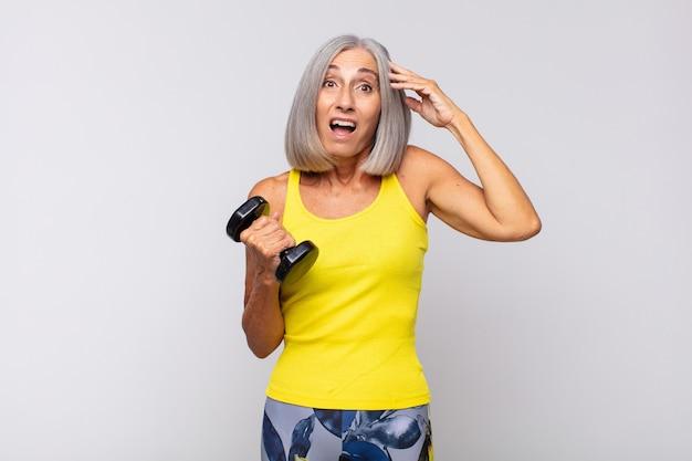 Femme d'âge moyen à la recherche de bonheur, étonné et surpris, souriant et réalisant une bonne nouvelle incroyable et incroyable
