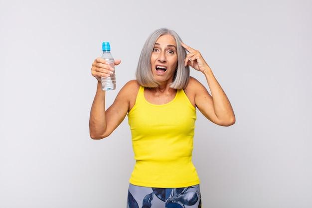 Femme d'âge moyen à la recherche heureuse, étonnée et surprise, souriante et réalisant une bonne nouvelle incroyable et incroyable. concept de remise en forme