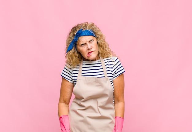Femme d'âge moyen à la recherche perplexe et confuse, mordant la lèvre avec un geste nerveux, ne sachant pas la réponse au concept de femme de ménage de problème