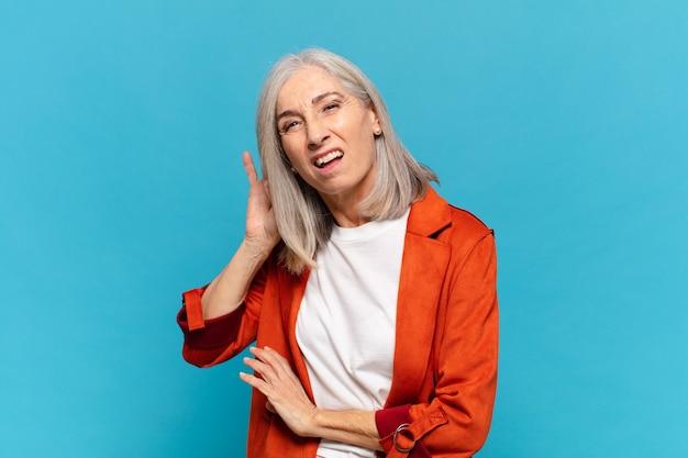 Femme d'âge moyen à la recherche sérieuse et curieuse, à l'écoute, en essayant d'entendre une conversation secrète ou des potins, une écoute clandestine