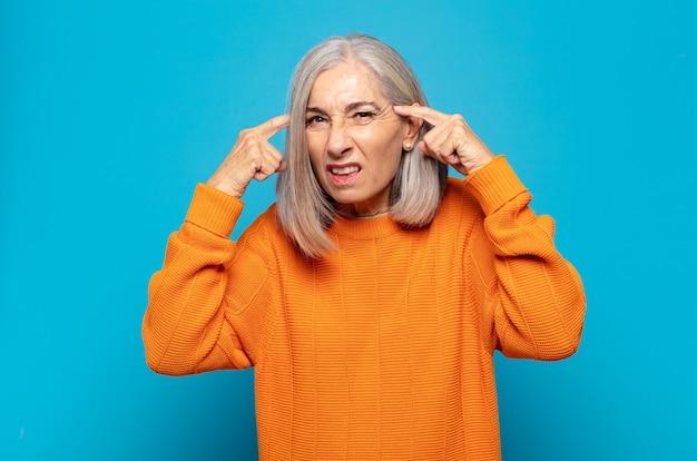 Femme d'âge moyen avec un regard sérieux et concentré, remue-méninges et réflexion sur un problème difficile