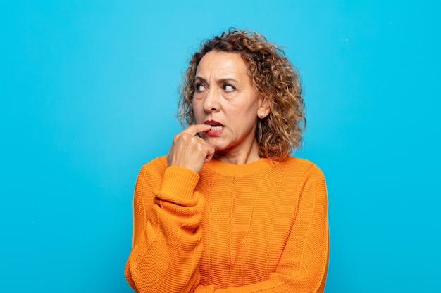 Femme d'âge moyen avec un regard surpris, nerveux, inquiet ou effrayé, regardant de côté vers l'espace de copie