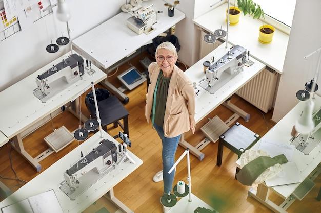 Une femme d'âge moyen regarde la caméra debout près des machines à coudre dans un studio spacieux