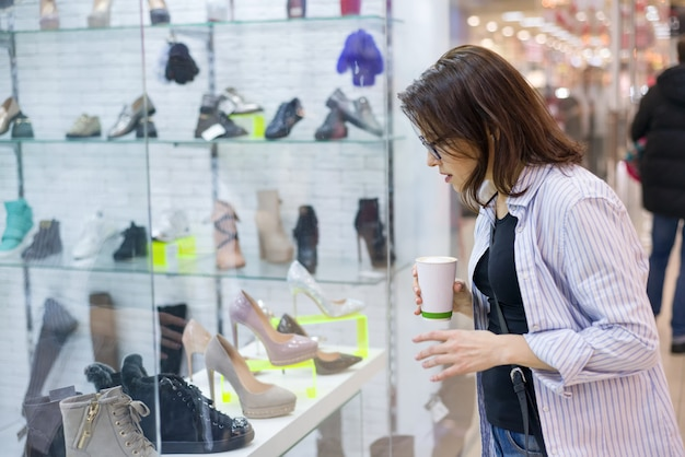 Femme d'âge moyen regarde la vitrine de la chaussure dans le centre commercial