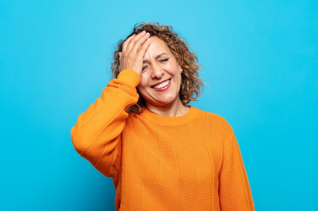 """Femme d'âge moyen riant et giflant le front comme dire dã ¢ â € âšãƒâ """"ãƒâ´oh! j'ai oublié ou c'était une erreur stupide"""