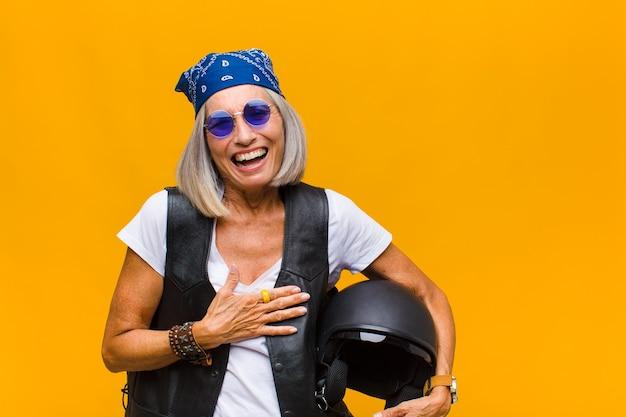 Femme d'âge moyen rire aux éclats à une blague hilarante, se sentir heureux et joyeux, s'amuser