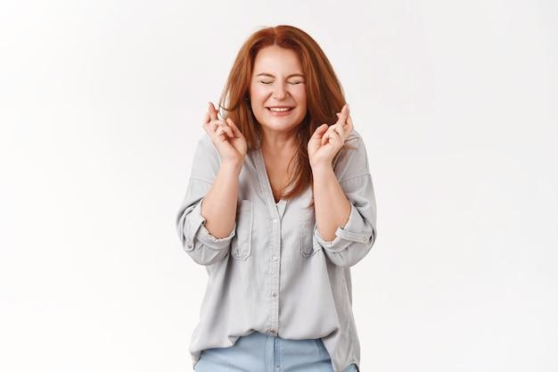 Femme d'âge moyen rousse pleine d'espoir faisant des vœux croisant les doigts bonne chance yeux fermés sincère heureux sourire excité croire que le rêve se réalise suppliant prier des résultats positifs, mur blanc