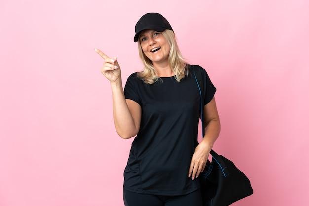 Femme d'âge moyen avec sac de sport isolé sur mur rose doigt pointé sur le côté et présentant un produit