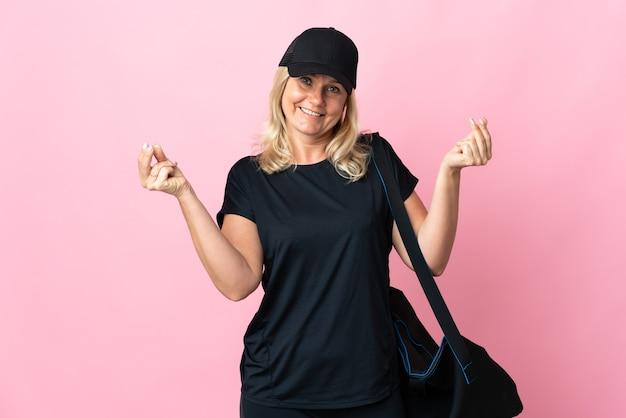Femme d'âge moyen avec sac de sport isolé sur mur rose faisant un geste d'argent