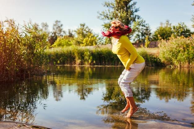 Femme d'âge moyen, sauter sur la rive du fleuve le jour de l'automne bonne dame senior s'amuser