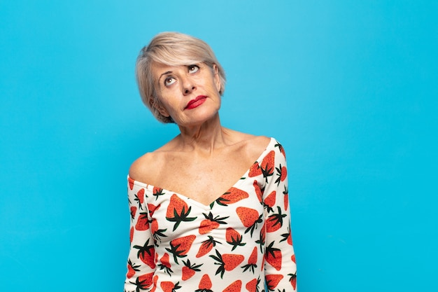 Femme d'âge moyen se demandant, pensant des pensées et des idées heureuses, rêvant, cherchant à copier l'espace sur le côté
