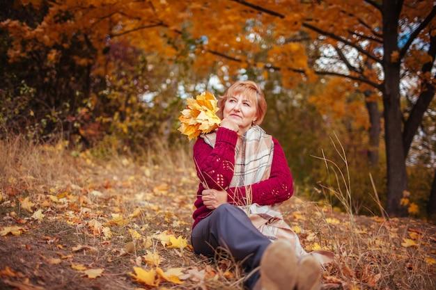 Femme d'âge moyen se détend dans la forêt d'automne.