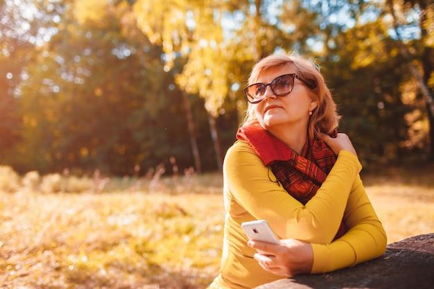 Femme d'âge moyen se détendre en utilisant un téléphone à l'extérieur