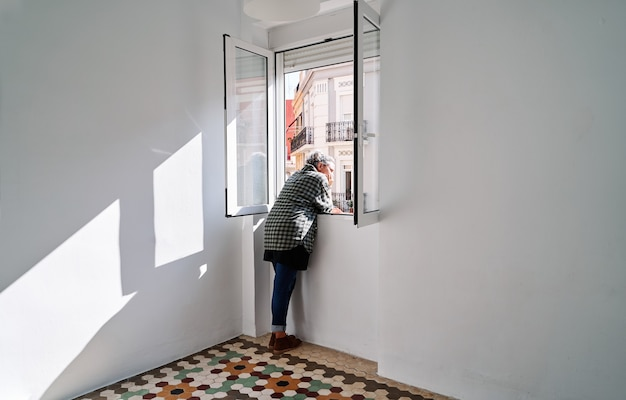 Une femme d'âge moyen se penche par la fenêtre dans une pièce avec un sol hydraulique coloré
