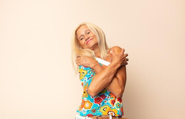 Femme d'âge moyen se sentant amoureuse, souriante, se câlinant et s'embrassant, restant célibataire, égoïste et égocentrique