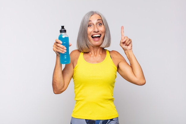 Femme d'âge moyen se sentant comme un génie heureux et excité après avoir réalisé une idée, levant joyeusement le doigt, eureka!. concept de remise en forme