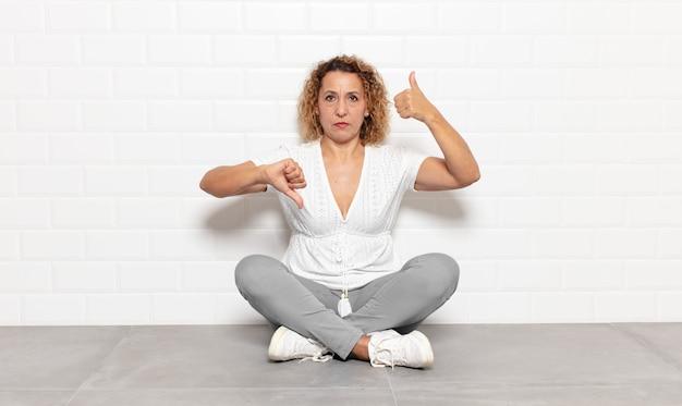 Femme d'âge moyen se sentant confuse, désemparée et incertaine, pondérant le bien et le mal dans différentes options ou choix
